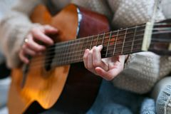 Play the guitar by hand Artist or musician.Young woman hands in knitted sweater. Home music party. Play the guitar by hand Artist or musician Royalty Free Stock Image