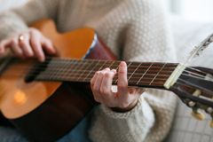 Play the guitar by hand Artist or musician.Young woman hands in knitted sweater. Home music party. Play the guitar by hand Artist or musician Stock Images