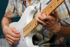 Play on guitar, selective focus on part of strings Royalty Free Stock Photos