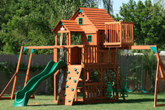 Play house swings and slide. Scenic view of wooden play set in garden with playhouse, slide, swings and climbing apparatus Stock Images