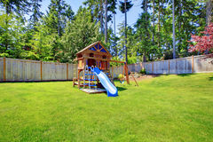 Play kids ground area with chute in fenced backyard. Stock Photo
