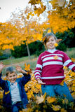 Play with leaves. Two kids playing with autumn yellow leaves stock image