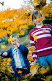 Play with leaves. Two kids playing with autumn yellow leaves royalty free stock images