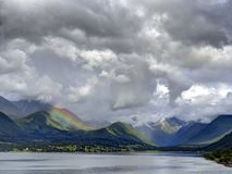 Play of Light over Geirangerfjord, Norway. Rain clouds and play of light over hills of Geirangerfjord, a fjord in Norway, which is a UNESCO World Heritage Site Royalty Free Stock Images