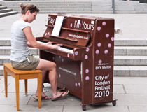 Play me I'm Yours,Street Pianos. A young women plays one of the street pianos left as the art installation Play Me I'm yours by Luke Jerram. The pianos are part Stock Photo