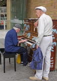 Play me I'm Yours,Street Pianos. A senior man plays one of the street pianos while his companion listens. The piano in Liverpool street station is part of an art Royalty Free Stock Image