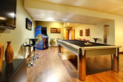 Play party room home interior with pool table. Fun play room home interior. Basement room without windows with pool table, TV, games royalty free stock image
