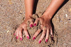 Play in sand. Woman hands in the wet sand Stock Photo