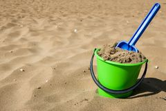 Play in sand. Green plastic bucket and blue shovel on a beach. Concept for traveling with children / family vacation and holiday. Copy space royalty free stock photography