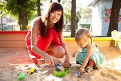 Play in the sandbox. Mother and baby daughter playing in the sandbox Stock Photos