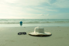 Play on the sea. White hat and sun glasses place on the beach Stock Photos