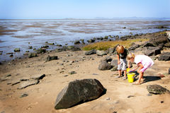 Play on the shore. Two little elementary aged kids, a boy and a girl, playing in the sand and tide pools on the shore at the beach with territorial hills in the Stock Images