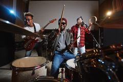 Play, sing and record. Band of young drummer, guitarist and singer playing instruments and performing songs in studio of records stock image