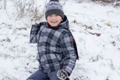 Play the snowball boy. The boy laughs and throws snowballs in the winter Stock Image