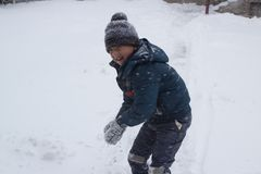 Play the snowball boy. In winter, the boy climbs in the hands of a snowball to play Royalty Free Stock Photography