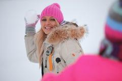 Play snowballs. Winter women play snowballs on snow background stock photo