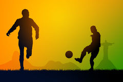 Play soccer. Silhouette soccer players to the sunset time Royalty Free Stock Image
