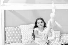 Play soft toy before go sleep. Girl long curly hair enjoy evening time with favorite toy. Kid sit bed and play bunny toy. Modern bedroom interior. Evening time stock photos
