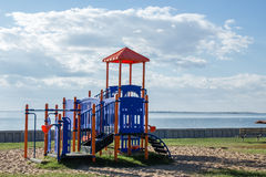 Play structure sitting next to a big lake in summer. Horizontal image of a play structure sitting near a big lake under a blue sky with clouds in the summer Royalty Free Stock Photography