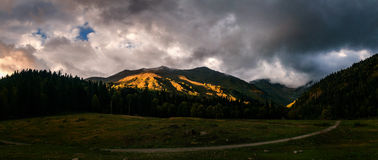 Play of sunset light and shadow on mountain Stock Images