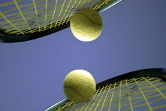 Play tennis. Two Tennis rackets with yellow tennis balls outdoors and sky blue royalty free stock photography