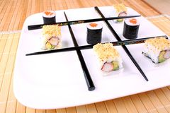 Play tic tac toe with sushi and chopsticks. Close up Stock Photo