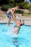 Play Time. A young boy being thrown up in the pool Stock Images