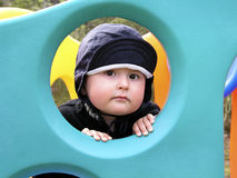Play time. Young boy playing outside, posing through a hole in a climber royalty free stock images