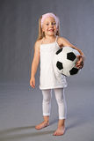 Play time. Cute little girl holding a ball and looking ready to play. Studio shot on grey Royalty Free Stock Photo