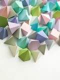 Play time. Colorful abstract geometric background with three-dimensional solid figures. Pyramid Dodecahedron prism rectangular cube arranged on white paper Royalty Free Stock Image