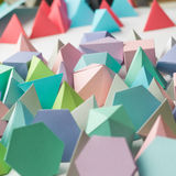 Play time. Colorful abstract geometric background with three-dimensional solid figures. Pyramid Dodecahedron prism rectangular cube arranged on white paper Stock Image
