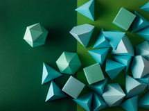 Play time. Colorful abstract geometric background with three-dimensional solid figures. Pyramid Dodecahedron prism rectangular cube arranged on green paper Royalty Free Stock Image