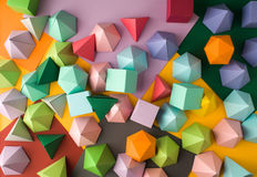 Play time. Colorful abstract geometric background with three-dimensional solid figures. Pyramid Dodecahedron prism rectangular cube arranged on colored paper Royalty Free Stock Images