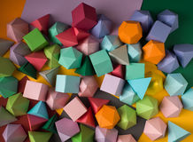 Play time. Colorful abstract geometric background with three-dimensional solid figures. Pyramid Dodecahedron prism rectangular cube arranged on colored paper Royalty Free Stock Image