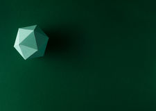 Play time. Paper dodecahedron on green background Royalty Free Stock Photos