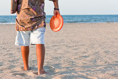 Play to frisbee on the beach in summer. Person of shoulders on the sand playing to frisbee Royalty Free Stock Photo