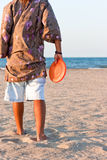 Play to frisbee on the beach in summer. Person of shoulders on the sand playing to frisbee Stock Photography