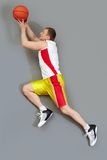 Play to win. Muscular basketball player slamming the ball, overview Royalty Free Stock Photo