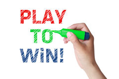 Play to Win Words Determination. Play to Win concept and green marker in hand Stock Images
