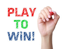 Play to Win Words Determination. Play to Win concept and green marker in hand Royalty Free Stock Images