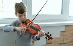 Play the violin. Seven years old boy playing the violin near a window. Front view. Play the violin. Seven years old boy playing the violin near a window. Front Stock Photo