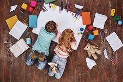 Play is the work of childhood. Children lying near books and toys, while drawing stock photos