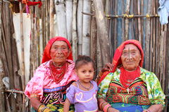 Playa奇哥村庄,巴拿马- 2014年8月, 4日:kuna印地安妇女的三世代当地服装出售的手工造衣裳 免版税库存照片