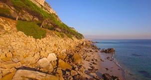 Playa aérea de la puesta del sol que viaja con las rocas almacen de metraje de vídeo