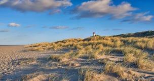 Playa abandonada con el faro detrás de las dunas imagenes de archivo