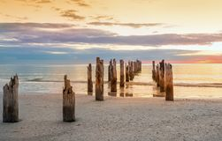 Playa abandonada y y los restos del embarcadero arruinado en el agua Fotos de archivo
