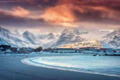 Playa arenosa ártica hermosa, mar y montañas nevosas en la puesta del sol Foto de archivo libre de regalías