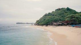 Playa arenosa blanca con los paraguas de la paja metrajes