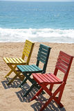 Playa arenosa de tres sillas de madera coloridas Imagenes de archivo