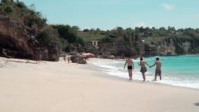 Playa arenosa del país de los sueños con las ondas espumosas y caminar de los turistas